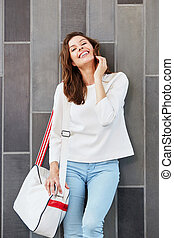 stylish young woman posing against a wall with bag