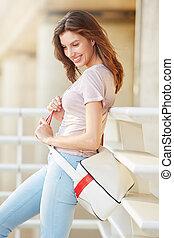 stylish young woman with handbag smiling outside