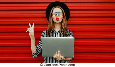 Portrait of stylish young woman with laptop over a red background