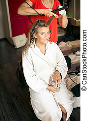 Portrait of stylist making hairstyle to elegant bride at...