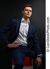 portrait of sublime rich well-off man in suit isolated on black background. male in classic wear has own business, sits on oil barrel. success concept