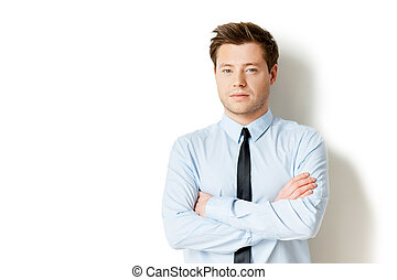 Portrait of success. Handsome young man in formalwear looking at camera and keeping arms crossed while standing isolated on white