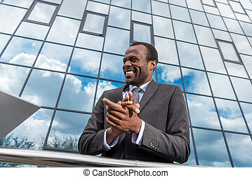 portrait of successful african american businessman laughing and gesturing while standing at office building