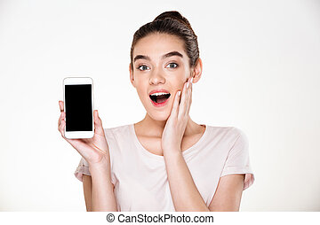 Portrait of successful brunette female 30s rejoicing her new modern smartphone showing it on camera over white wall