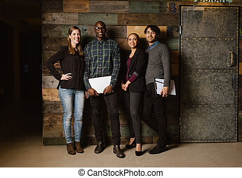 Portrait of successful business team standing in an office -...