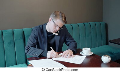 Portrait of successful businessman signing contract while having phone call in cafe.