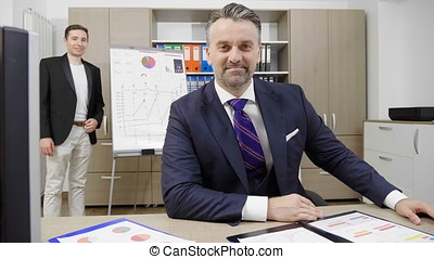 Portrait of successful businessman working in his busy office with his two colleagues in the background