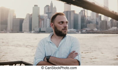 Portrait of successful European freelance businessman standing arms folded at Brooklyn Bridge New York river scenery 4K.