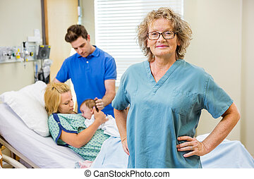 Portrait of successful mature nurse standing with couple and...