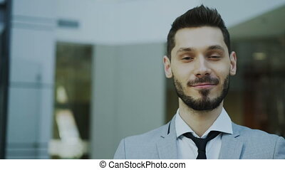 Portrait of successful young smiling businessman looking into camera in modern office