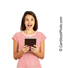 Portrait of surprised and impressed woman with widened eyes and opened mouth, stunned because of something she sees on screen of tablet. emotional girl isolated on white background