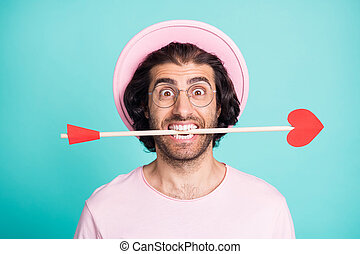 Portrait of surprised funny guy hold arrow in teeth wear spectacles pastel pink cap t-shirt isolated on teal color background