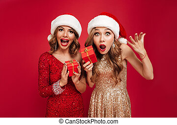 Portrait of surprised happy women in christmas hats