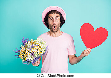 Portrait of surprised hipster guy hold flowers paper heart wear pink cap t-shirt spectacles isolated on teal color background