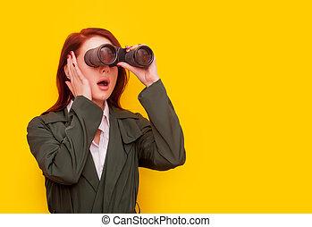 woman with binocular on yellow background
