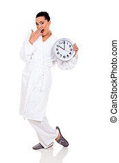 surprised young woman in pajamas with clock
