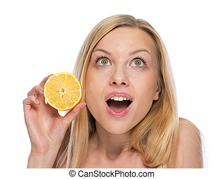 Portrait of surprised young woman with lemon looking on copy space