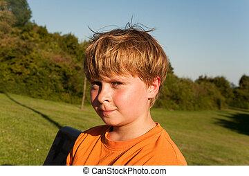 portrait of sweating boy after sports - child boy in orange...