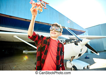 sweet little boy with toy plane playing outside on a beautiful sunny summer day