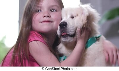 Portrait of sweet little girl cuddling with puppy - Closeup...