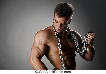 Studio portrait of tanned bodybuilder posing with chain