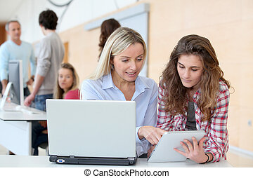 Portrait of teacher and teenage girl in computing class