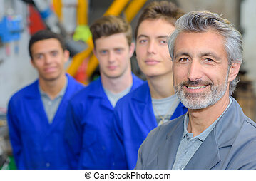 Portrait of teacher stood in front of his three apprentices