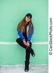 Portrait of teen girl near green wall in winter.
