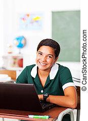 teen girl sitting in classroom using computer