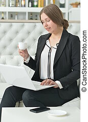 Portrait of teen girl wearing formal wear using laptop and...