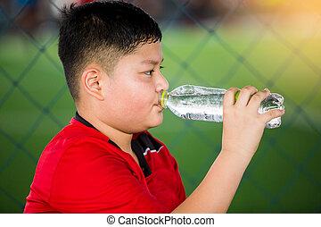 Portrait of teenage boy drinking water