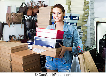 portrait of teenage girl standing with bags in store with bags