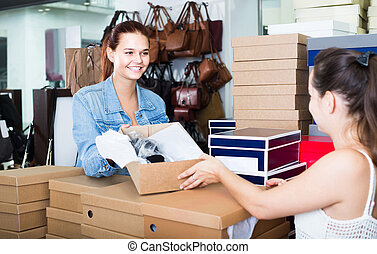 portrait of teenage girl talking to seller among boxes with new shoes in fashion store