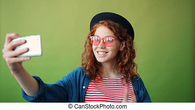 Portrait of teenager in hat and glasses taking selfie with smartphone camera
