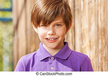 Portrait of ten years old boy in purple shirt
