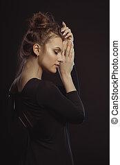 Portrait of tender brunette woman in the dark room