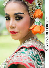 Portrait of Thai young lady wearing Thai traditional dress in the garden