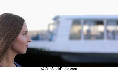 Portrait of the attractive young woman with long straight hair on the background of the boat in the bay