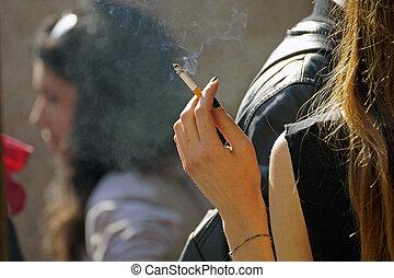 Portrait of the beautiful elegant girl smoking cigarette.