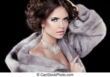 Portrait of the beautiful fashion woman wearing in mink fur coat with wavy hair styling. Jewelry accessories.