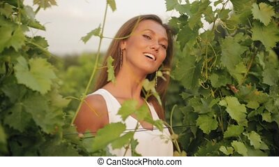 Portrait of the beautiful girl in the leaves of the vine