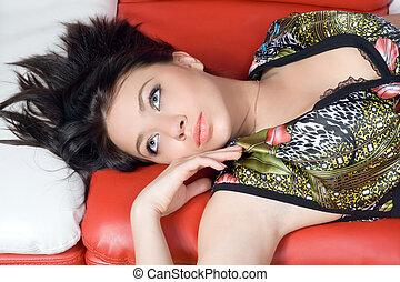 Portrait of the beautiful girl lying on a sofa