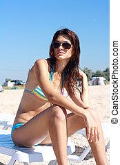 beautiful girl sitting sea on coast