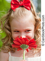 Portrait of the beautiful little girl with a red flower