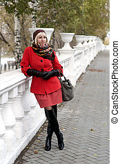 Portrait of the beautiful Russian woman in the fall in the park.