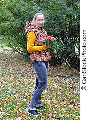 Portrait of the beautiful Russian woman with flowers in the park