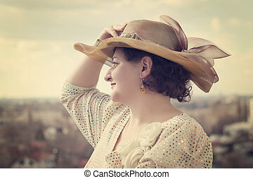 Portrait of the beautiful smiling woman looking thoughtfully in a distance
