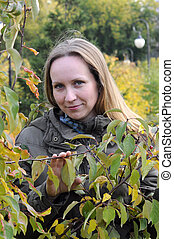 Portrait of the beautiful woman against autumn leaves.