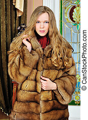 Portrait of the beautiful woman in fur coat. The luxurious ...