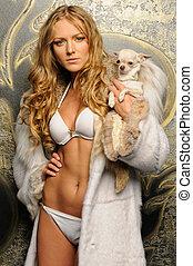 beautiful woman in fur coat with chihuahua dog.